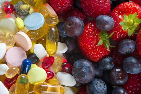 An image of supplements on the left side and strawberries and blueberries on the right side.